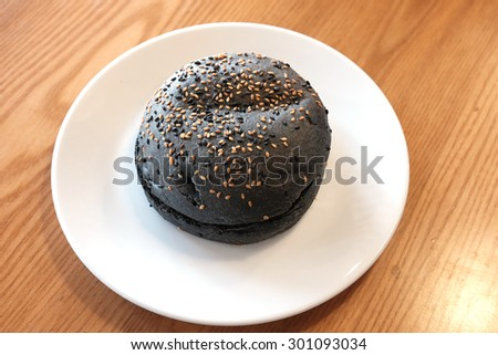 Tasty black buns with sesame on white plate, on wooden background - stock photo
