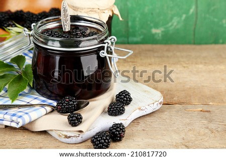 Tasty blackberry jam and fresh berries, on wooden table - stock photo
