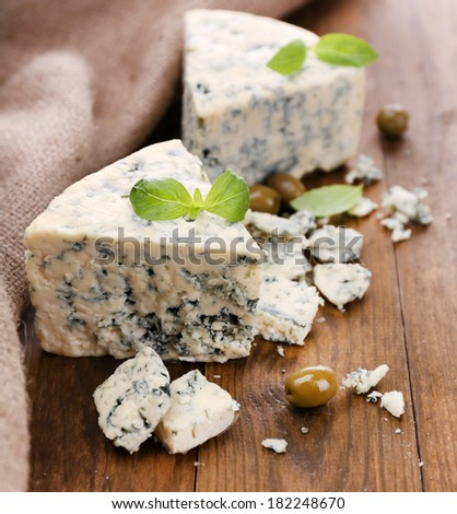 Tasty blue cheese with olives and basil, on wooden table - stock photo