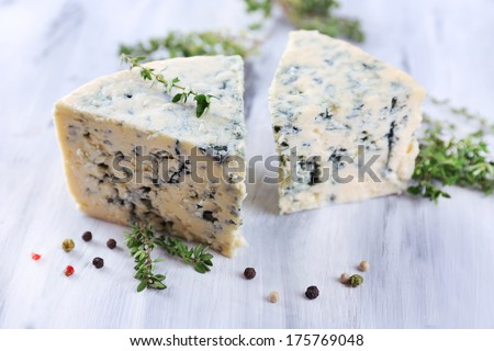 Tasty blue cheese with thyme and spices on wooden table - stock photo