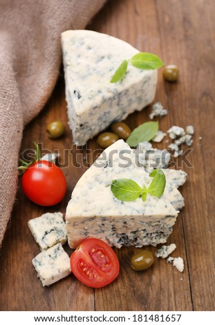 Tasty blue cheese with tomato, olives and basil, on wooden table
