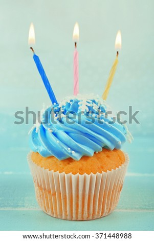 Tasty blue cupcakes decorated with candles on light background