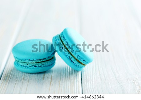 Tasty blue macarons on a blue wooden table - stock photo