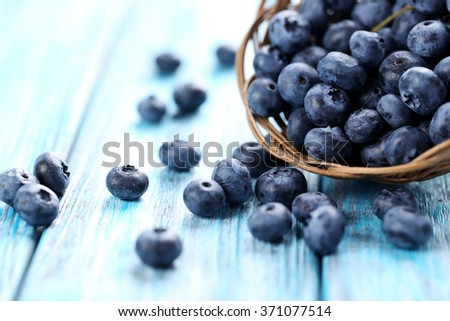 Tasty blueberries in basket on a blue wooden table - stock photo