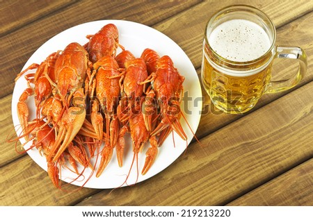 Tasty boiled crayfish and beer on a table - stock photo