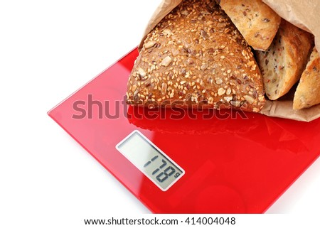 Tasty bread on digital kitchen scales, isolated on white - stock photo