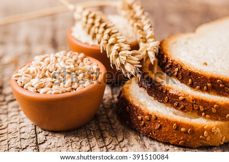 Tasty bread with sesame seeds.fresh wheat grains and flour.Slices of bread - stock photo