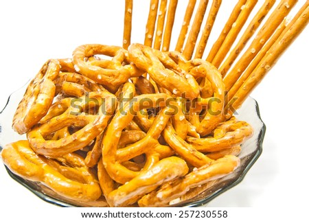 tasty breadsticks and salted pretzels closeup on white - stock photo