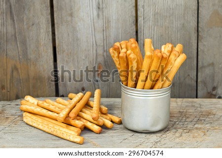 Tasty breadsticks grissini in iron cup. Food on wooden background - stock photo
