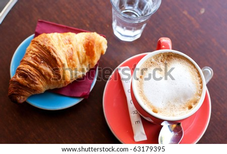 Tasty breakfast in a Parisian street cafe - cup of coffee, croissant and glass of water - stock photo