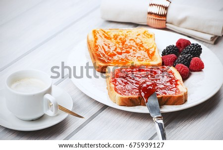 Tasty breakfast of toast with strawberry and peach jam along with blackberries and raspberries, and a cup of coffee.