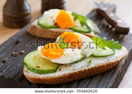 Tasty breakfast or snack toasts with cream cheese, fresh sliced cucumber and boiled egg, garnished with arugula leaves and spices on wooden cutting board. Selective focus - stock photo
