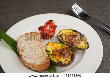 Tasty breakfast with avocado baked, top view