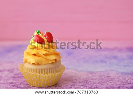 Tasty bright cupcake on color background