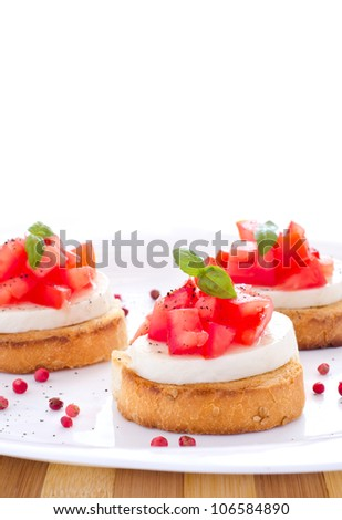 Tasty bruschetta with bread tomatoes basil and cheese and white space - stock photo