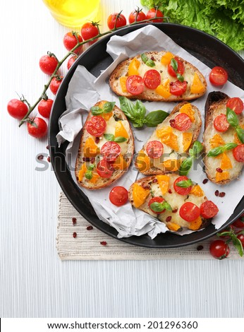 Tasty bruschetta with tomatoes in pan, on table