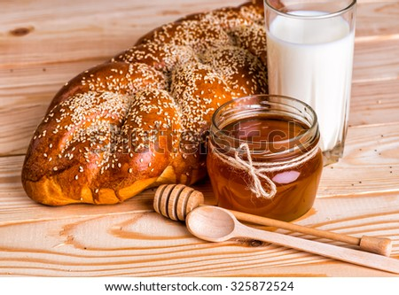 tasty buns with poppy and sesame milk and honey on wooden background