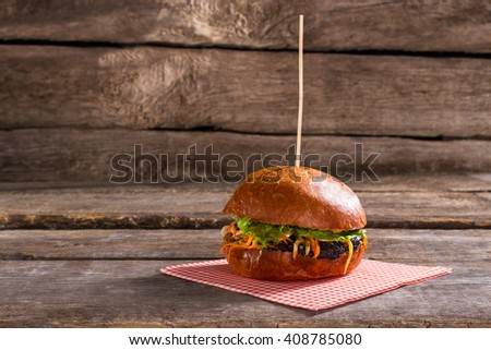 Tasty burger on stick. Old table with delicious hamburger. Grilled beef and fresh buns. Try the taste of energy. - stock photo