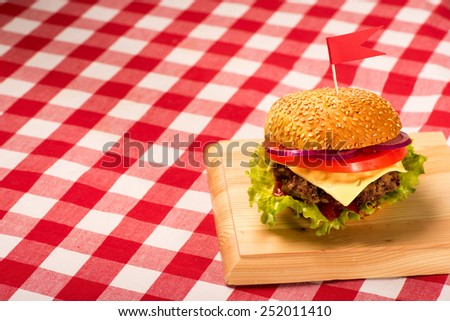 Tasty burger with flag, french fries and beverage on wooden board - stock photo