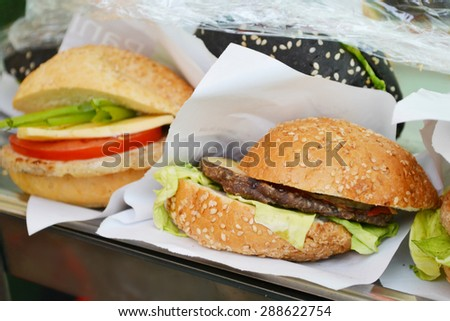 Tasty burger with meat, salad and tomato - stock photo