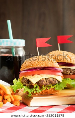 Tasty burgers with flags, french fries and beverage on wooden board - stock photo
