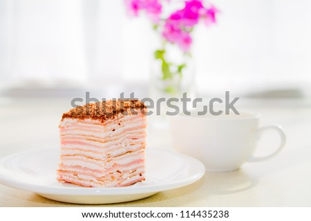 Tasty cake on the plate with cup of cofee and flowers in background - stock photo