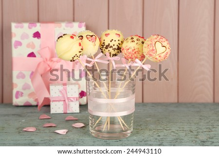 Tasty cake pops and gifts on wooden background - stock photo
