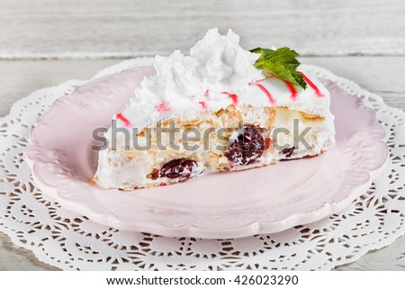 Tasty Cake with cream mascarpone and cherries on plate, on a light wooden background. Selective focus - stock photo