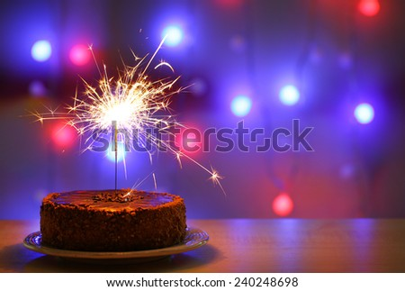 Tasty cake with sparkler on shiny background - stock photo