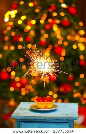 Tasty cake with sparkler on table, on shiny background - stock photo