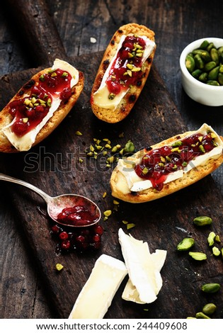 Tasty camembert and cranberry coulis sprinkled with chopped fresh pistachio nuts on toasted rolls being prepared in the kitchen, with copyspace - stock photo