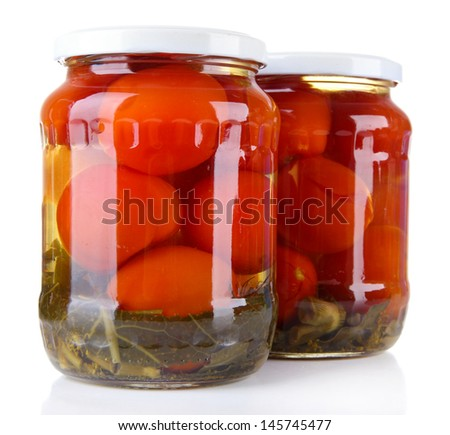 Tasty canned tomatoes in glass jars, isolated on white