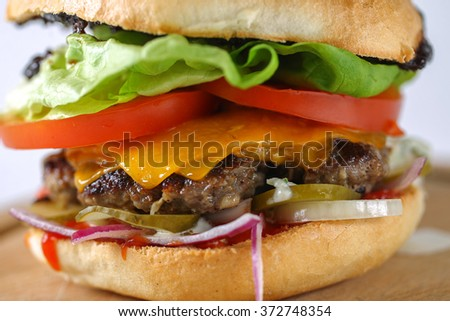 Tasty cheese beef burger with lettuce, cheddar, barbecue sauce, tomatoes, pickles and tzatziki