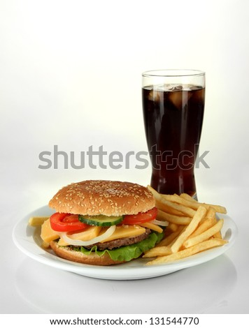 Tasty cheeseburger with fried potatoes and cold drink, isolated on white - stock photo