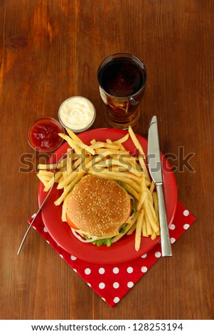 Tasty cheeseburger with fried potatoes and cold drink, on wooden background - stock photo
