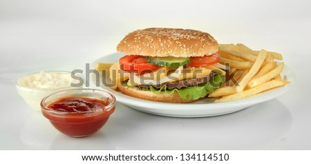 Tasty cheeseburger with fried potatoes, isolated on white - stock photo