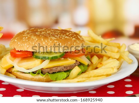 Tasty cheeseburger with fried potatoes, on bright background