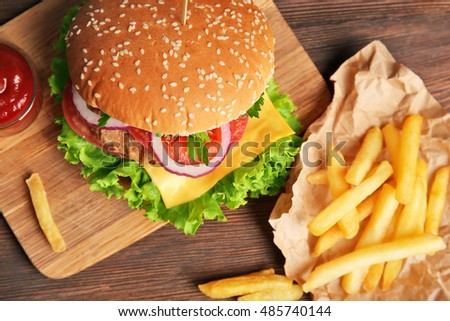 Tasty cheeseburger with fries on wooden table