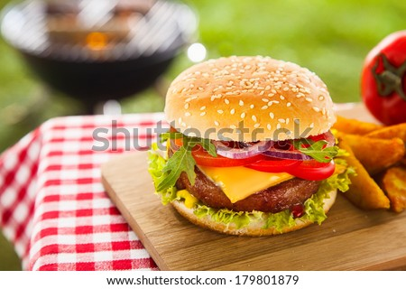 Tasty cheeseburger with melted cheddar cheese dripping over ground beef burger garnished with fresh salad ingredients and served on a wooden table on an outdoor picnic table