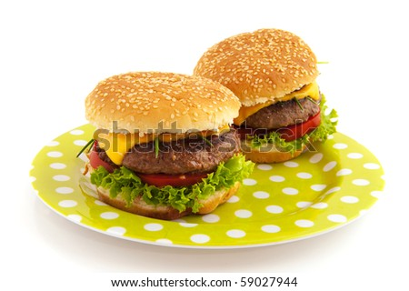 Tasty cheeseburgers with vegetables on a dotted plate