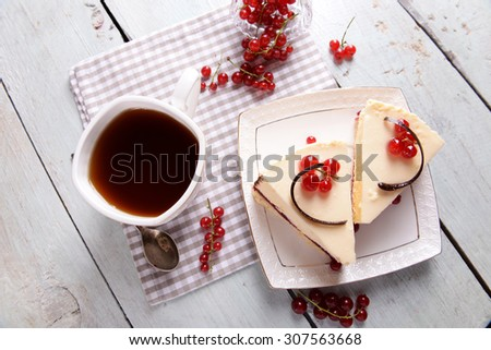 Tasty cheesecake with berries and cup of tea on table close up - stock photo