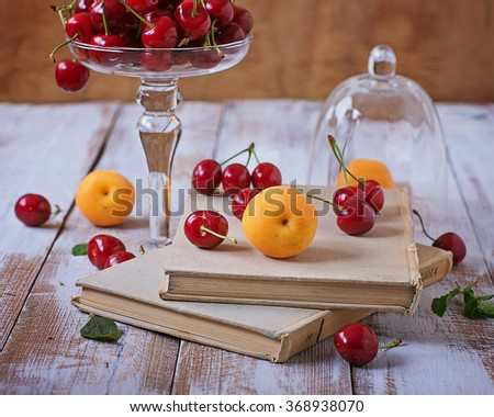 Tasty cherry, apricots and old books on a wooden table - stock photo