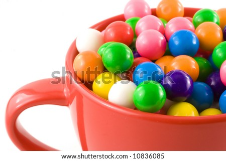 Tasty, chewy, sweet bubble gum balls rest inside a bright red cup. - stock photo