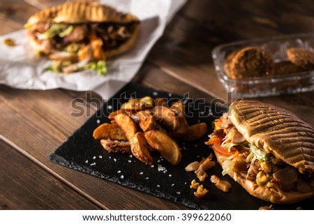 Tasty chicken doner kebab with fried potato on a wooden table with falafel - stock photo