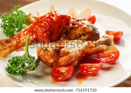 Tasty chicken legs with tomato sauce on plate, closeup