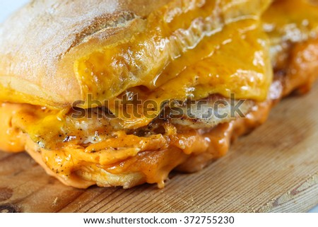 Tasty chicken steak sandwich in a ciabatta with cheddar cheese and thick romanian garlic sauce - stock photo