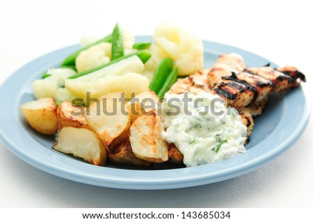 tasty chicken tenders souvlaki grilled with roast potatoes and fresh vegetables and tzatziki - stock photo