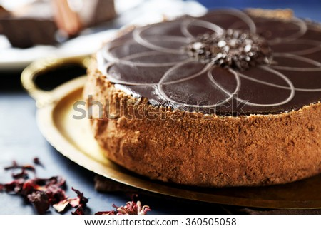 Tasty chocolate cake on tray, on color wooden background - stock photo