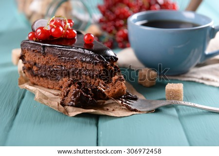 Tasty chocolate cake with berries and cup of tea on table close up - stock photo