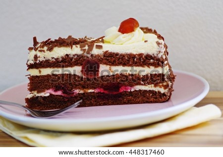 Tasty chocolate cake with cream and cherry on a soft pink plate on a wooden served table. - stock photo
